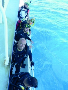 Scuba divers lining up on MV SeaEstas starboard side getting ready to jump in the water
