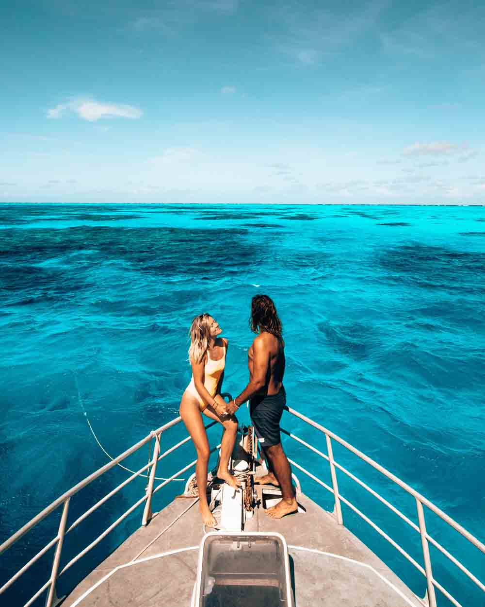 a blonde long-haired woman and dark long-haired male standing at the bow of MV Adrenalin overlooking Lodestone Reef