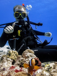Scuba diver posing with a thumbs up whilst a clownfish swims in the foreground