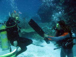 Photo of a scuba diver handing her buddy her fin underwater