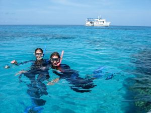 Two Snorkellers on the Great Barrier Reef Liveaboard with MV SeaEsta in the background