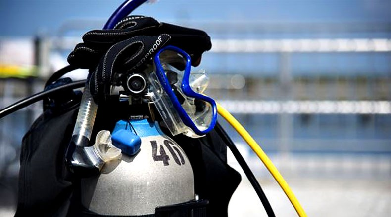 BCD and regulator attached to scuba tank with mask and dive gloves placed on top