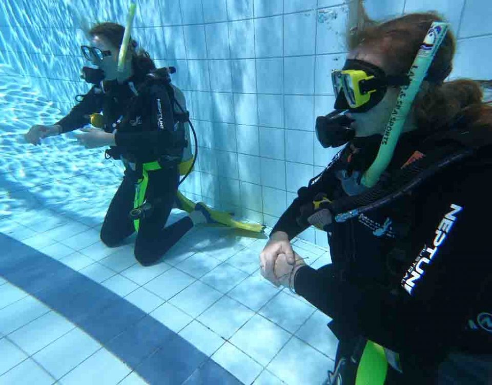 two female open water students underwater in a 3-metre pool