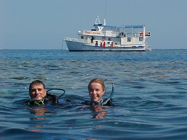 two scuba divers with their heads above the water with MV SeaEsta in the background