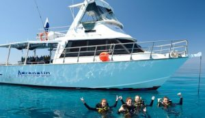 scuba divers on surface posing with MV adrenalin in background