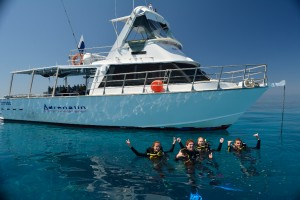 scuba divers on the surface of the water in front mv adrenalin posing for a photo