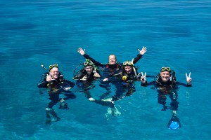 group of 4 dives posing with their dive guide on the surface of the water at lodestone reef