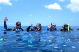 three introductory scuba divers and their instructor on the surface of the water after their dive posing with the OK sign