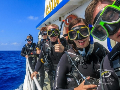 fully suited scuba divers standing on port side of a boat getting ready to jump in the water for their dive