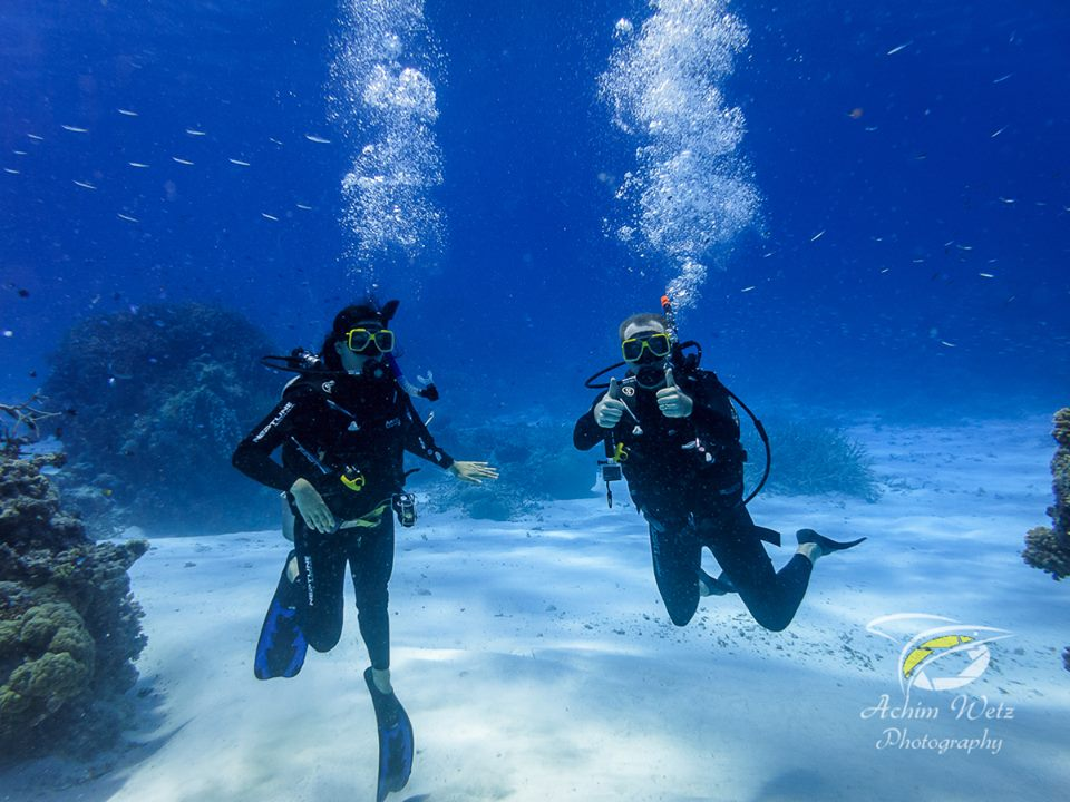 one female and one male scuba diver underwater floating just above the sandy bottom posing for the camera