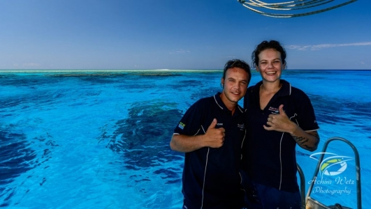 Crew members Achim and Ella posing for a picture with the reef behind them