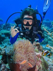 scuba diver posing behind anemone with ok hand sign