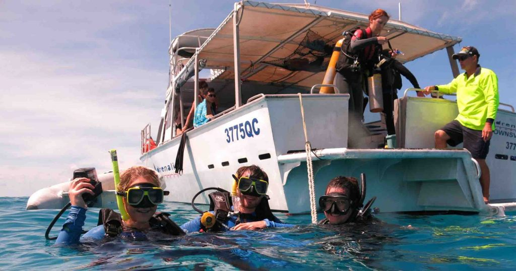 advanced open water students on the surface of reef