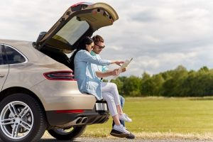 heterosexual couple sitting on the boot of their hatchback looking at a map