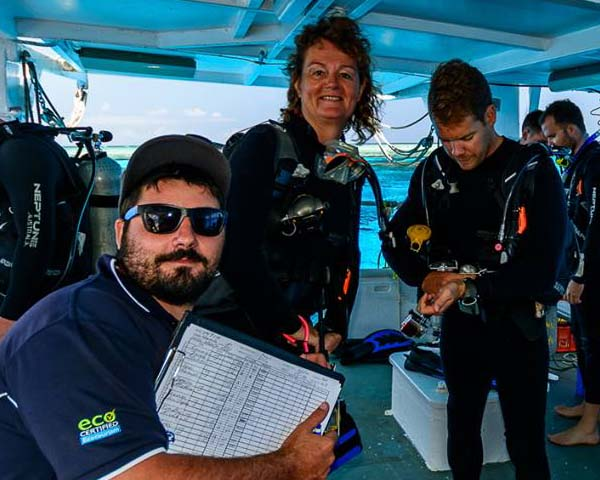 crew member posing with clipboard in front of two divers