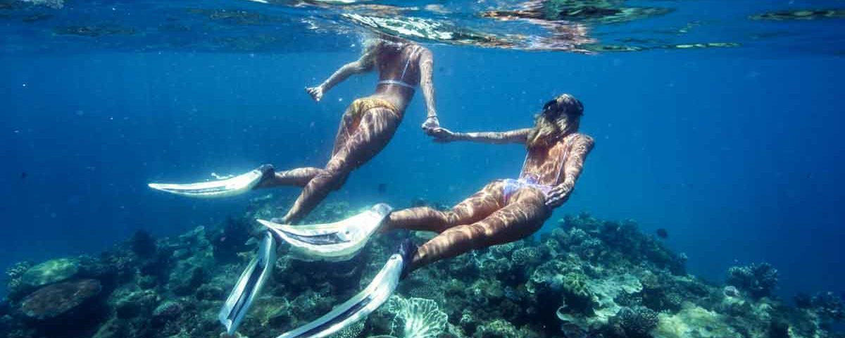 Two bikini-wearing snorkellers holding hands whilst snorkelling