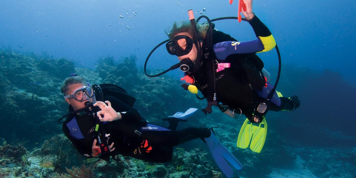 """two divers underwater with one holding the float line and the other holding up the """"all good"""" signal"""