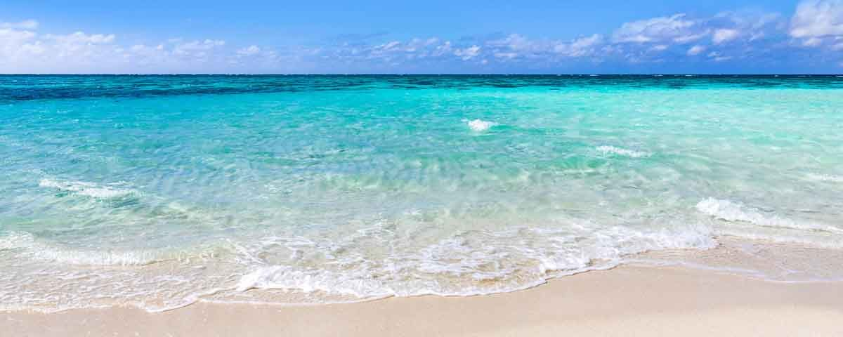 crystal clear waters as the waves lap against a sandy white beach