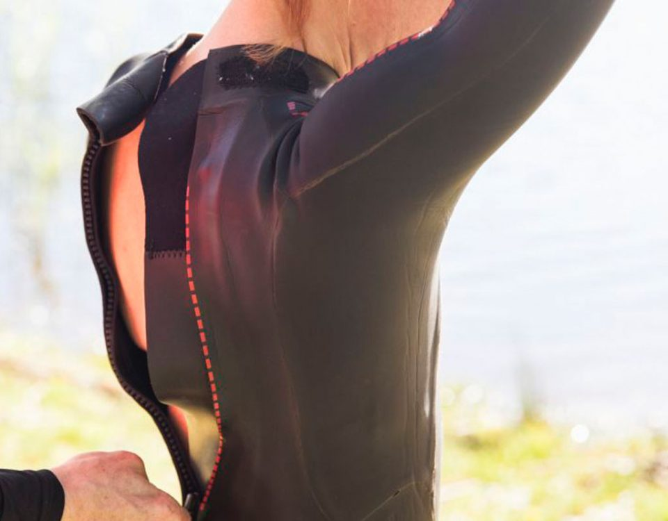 back shot of a woman zipping up a wetsuit with the help of another person
