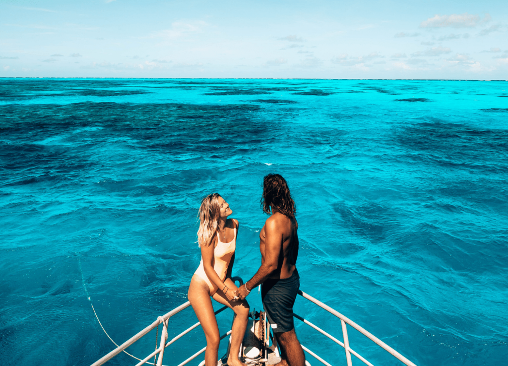 Two people on boat over reef